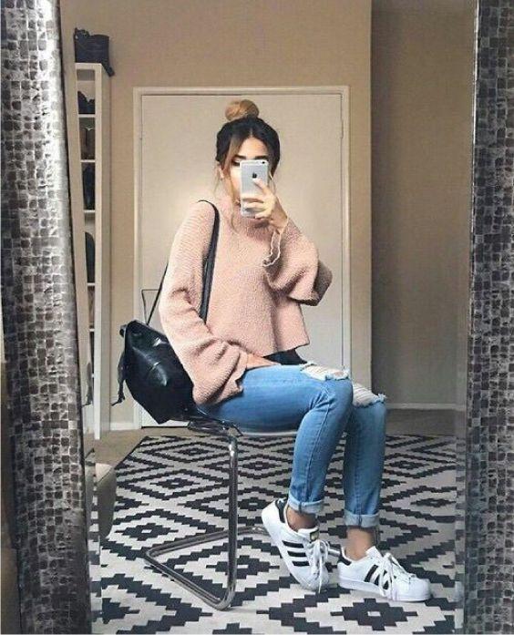Suéter rosa, calça jeans rasgada no joelho, tênis adidas branco