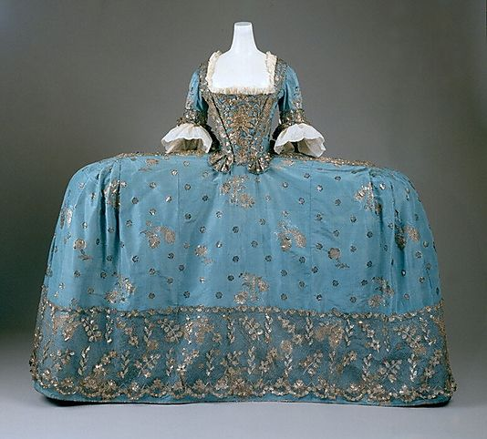 Court Dress, ca. 1750. British, silk, metallic thread. Universally described as the robe à la française, In its most formal configuration, it presented a wide and flattened profile accomplished by enlarged panniers. Constructed of supple bent wands of willow or whalebone and covered in linen, panniers took on broader or narrower silhouettes. The most remarkable held out the skirts like sandwich boards, barely wider than the body in side view but as expansive as possible in front or rear…