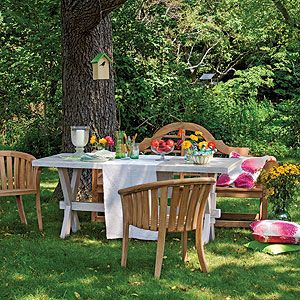 Outdoor furniture can become elegant setting with flowers, candles and linen.