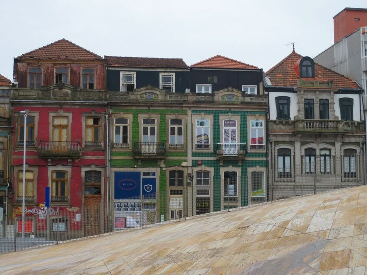 Contrasts the modern marble floor with in the back the old houses with the typical Portugese tiles