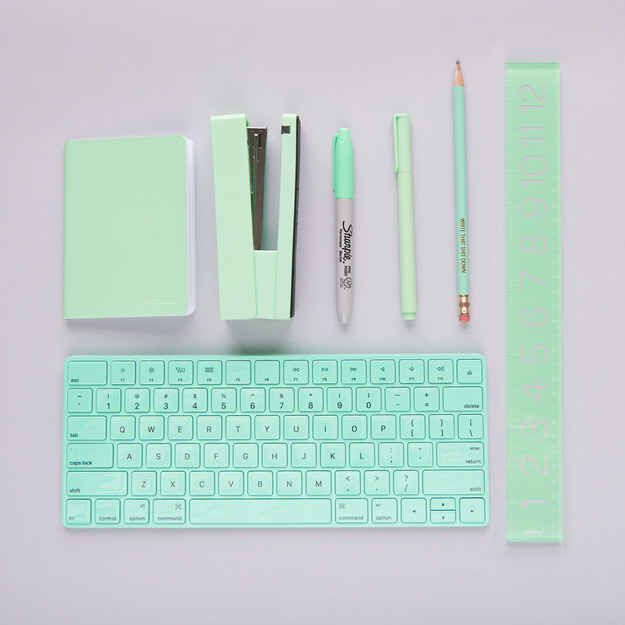 a photo of a turquoise keyboard, stapler, pen, pencil, notebook, sharpie, and ruler