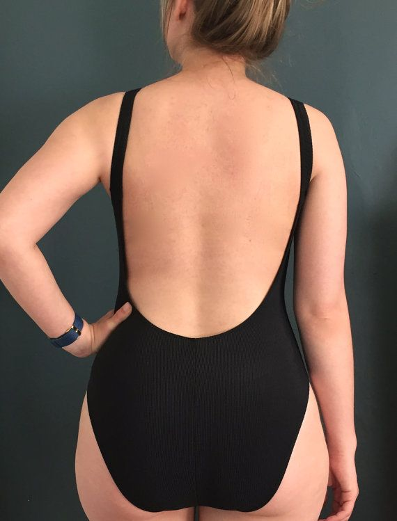 Vintage black ribbed 1-piece swim suit. Simple and modest but still flattering and classically sexy. This minimal bathing suit features a low-cut back and high-cut hip. SIZE Marked size: 10 Fits size: Medium  MATERIALS 84% nylon 16% spandex  CONDITION This vintage swimsuit is in great vintage condition. The suit is still very pigmented and elastic. However, the elastic in the built-in bra has deteriorated.