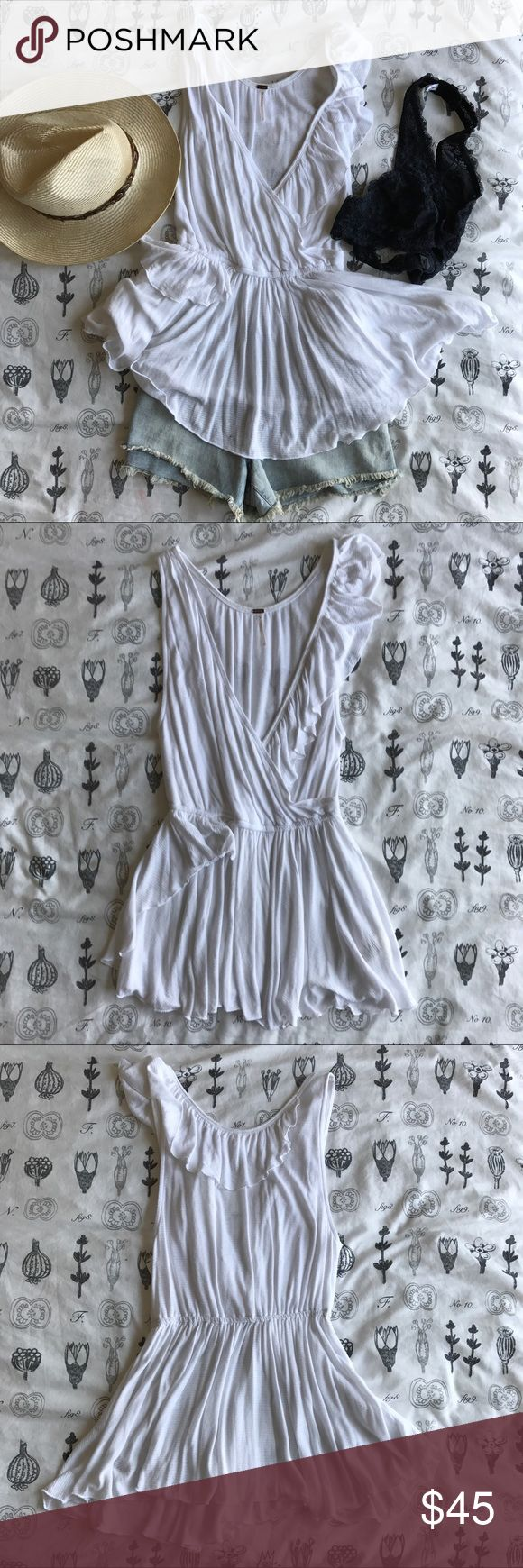 """NWOT Free People White Float Away Ruffle Top This Free People Float Away Ruffle Top is delicately draped with ruffle trimming and waist-defining top. Designed for a loose fit. Deep v-neck with asymmetric ruffle trim. Top is pullover style. 100% rayon. Length measures about 28"""". Free People Tops Tank Tops"""