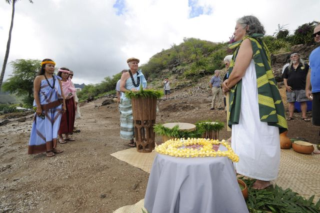 BRUCE ASATO / BASATO@STARADVERTISER.COM                                 Brad Cooper, center, presented the pahu drum, Kaniala'a, to Kaleo Paik, right, during a ceremony at the Hawea Heiau Complex site Sunday. Kaniala'a was crafted by Cooper using a piece of Coco, a coconut tree that, before its demise, stood 112 feet tall.