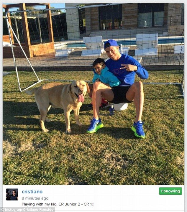Cristiano Ronaldo poses with his son Cristiano Jr after playing a game of football with the four-year-old.