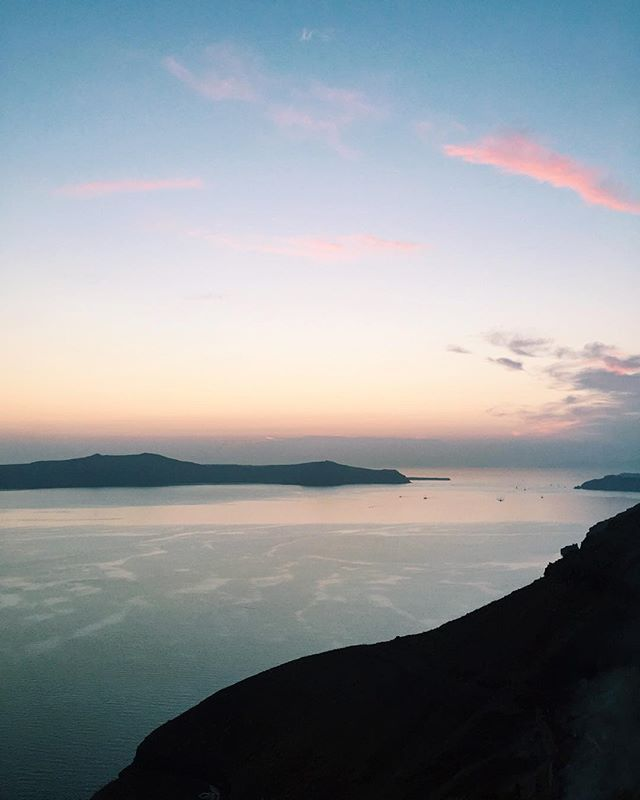 Cotton candy skies and a soft orange glow across the Aegean Sea