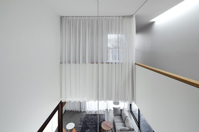 The void is veiled in sheer, white fabric that tracks around the perimeter, offering discretionary privacy.