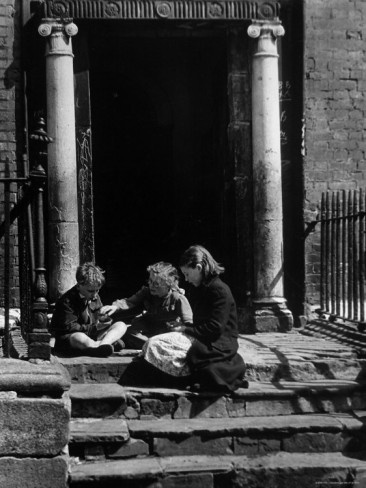 Children sitting on the steps of a Dublin slum