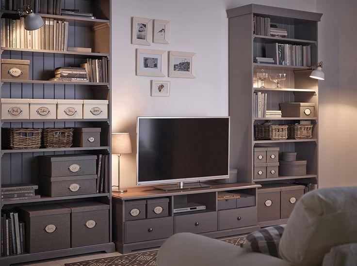 Séjour avec banc TV blanc à tiroirs flanqué de deux bibliothèques grises remplies de boîtes de rangement de différentes tailles et de livres