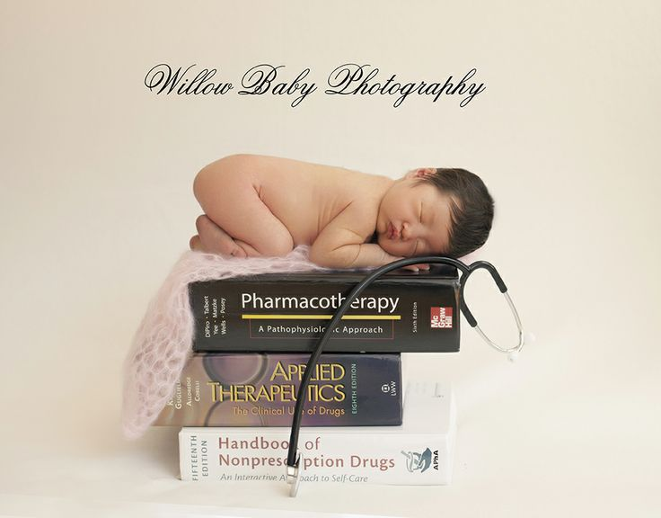 Newborn photography, baby doctor picture with baby on stack of medical books - newborn photos session at Willow Baby Photography