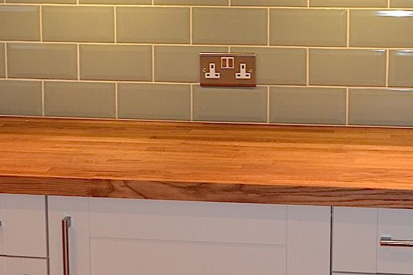 Solid Oak worktops, combined with the brick effect tiles offer a more traditional feel to this kitchen.