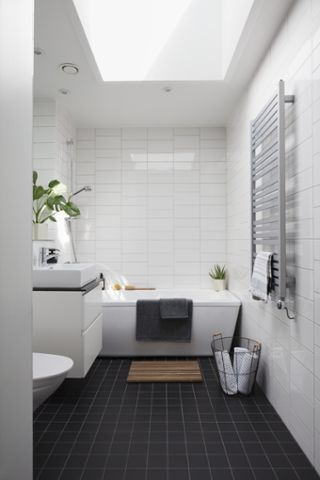 Clean white tiles against the wall, dark black tiles on the floor: the black and white bathroom trend at it's finest!