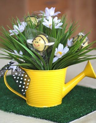 Bee cake pops in yellow watering can with daisies.