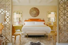 beautiful bedroom with mirrors behind lamps on bedside tables