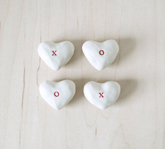 This is a listing for a set of 4 ceramic hearts.  : : Ready to ship : :  These hearts are unglazed, exposing the cream colored clay body stamped with a red X or O. They come in a little cotton drawstring bag with a hand painted red heart on it.  Hearts measure approx. 1.75 at widest part.  These make a great little gift for someone you love. They also make nice wedding favors or an engagement gift. Or just treat yourself and display them in a little bowl on your coffee table.  All of my…
