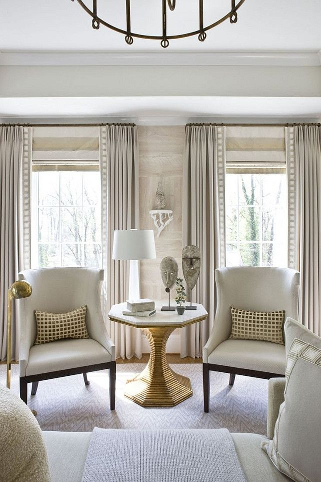 Living Room With Horizontal Stripe Roman Shade Mounted At Height Of Rod