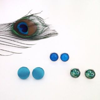 These gorgeous earrings are exclusively made for Brindie! Featuring the beautiful colours of peacock, this Trinket Trio of three pairs of earrings are easy to wear; so comfy and versatile!    Two pairs of earrings are hand-imaged 12mm glass domes set in silver tone stud findings.  The feature pair of studs are handmade turquoise satin buttons set on silver tone studs. These earrings are all lead and nickel free to be kind to sensitive ears.   The earrings are splashproof but not waterproof…