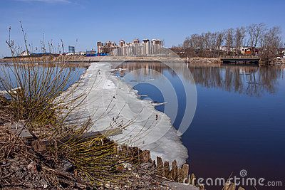 A large white ice floes along the blue river, and in it are reflected trees, houses, standing on the other side.