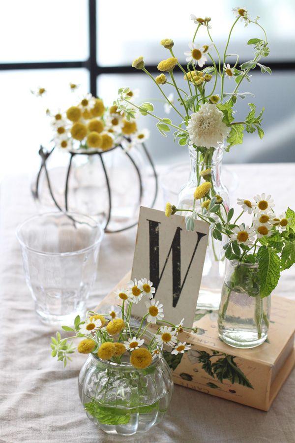 マトリカリアを形の違う小さな花瓶やボトルに生けたナチュラルな会場装花。