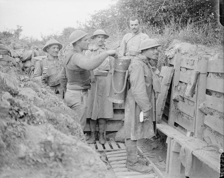 Portuguese troops helping themselves to hot food delivered in a carrier strapped on to a man's beck. Near Neuve Chapelle, 25 June 1917.