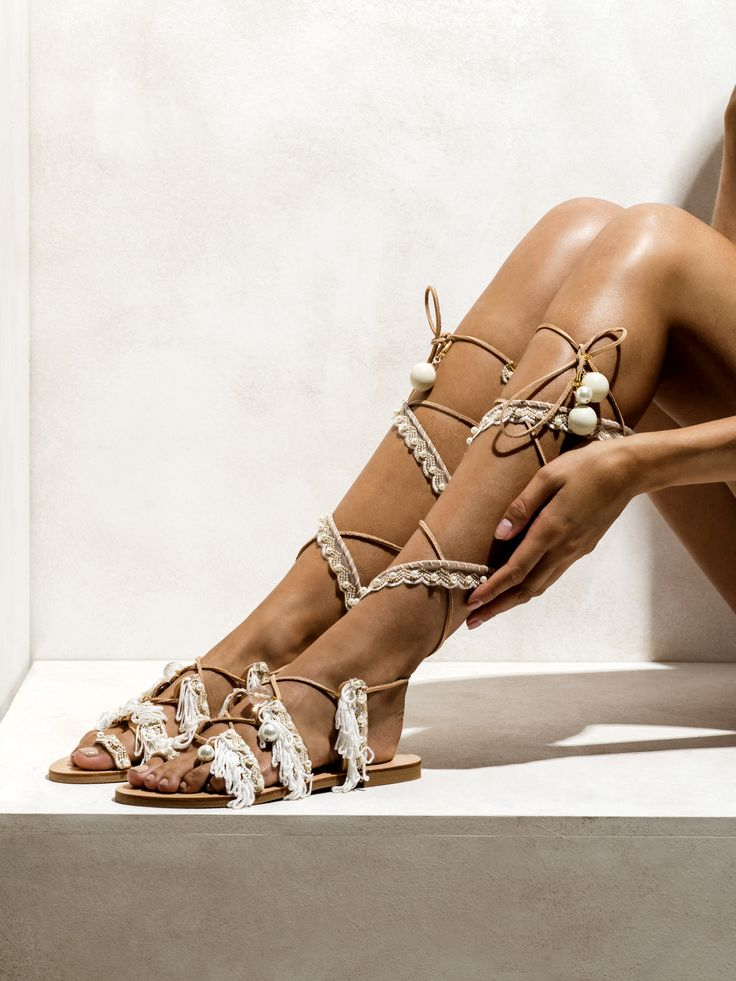 A truly ethereal and goddess-like pair of leather gladiator sandals decorated with sea shells, glass crystals, cotton fringes and a delicate lace, embroidered with small pearls.    http://www.elinalinardaki.com/shoes/sandals/all-time-classics/sandal-ever-after/