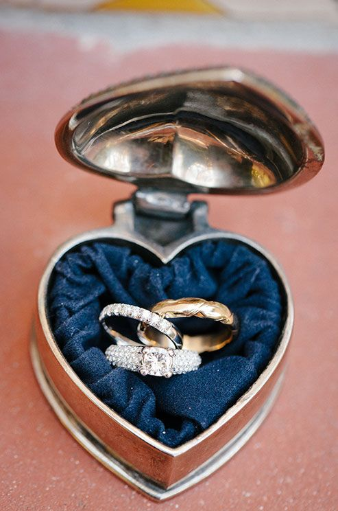 The bride and groom's wedding rings rest in a romantic, antique silver heart box.