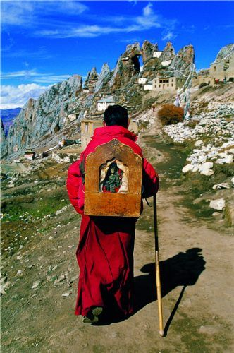 A monk carries a portable shrine on his back, Tibet