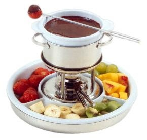 """1970s - Fondue parties were the rage.. """"Sweet or savory!  Dip pieces of fruit and marshmallows in melted chocolate, or crusty bread into melted cheese. Yummaroo."""""""