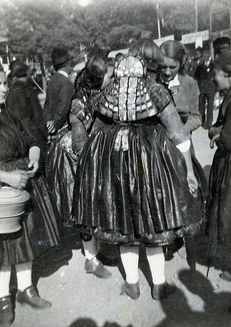 Frau in Schwälmer Tracht mit Brett in Ziegenhain, 1934 Rückenansicht einer Frau in Schwälmer Tracht. Dabei ist das sogenannte Brett, ein reich verzierter Rückenschmuck, gut zu erkennen. Im Hintergrund wird städtische Kleidung getragen. Das Bild entstand vermutlich bei der Salatkirmes in Ziegenhain.  in: Historische Bilddokumente <http://www.lagis-hessen.de/de/subjects/idrec/sn/bd/id/112-064> (Stand: 28.10.2013) #Schwalm