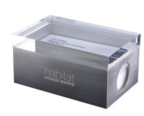 Stainless-steel business card holder with transparent acrylic top for viewing. A hole on the box's side allows for cards to be easily lifted. MoMA logo debossed on bottom. Proceeds from the sale of this MoMA product support the Museum programs.