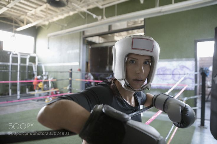 Portrait confident female boxer wearing protective headwear and boxing glove in boxing ring by HeroImages