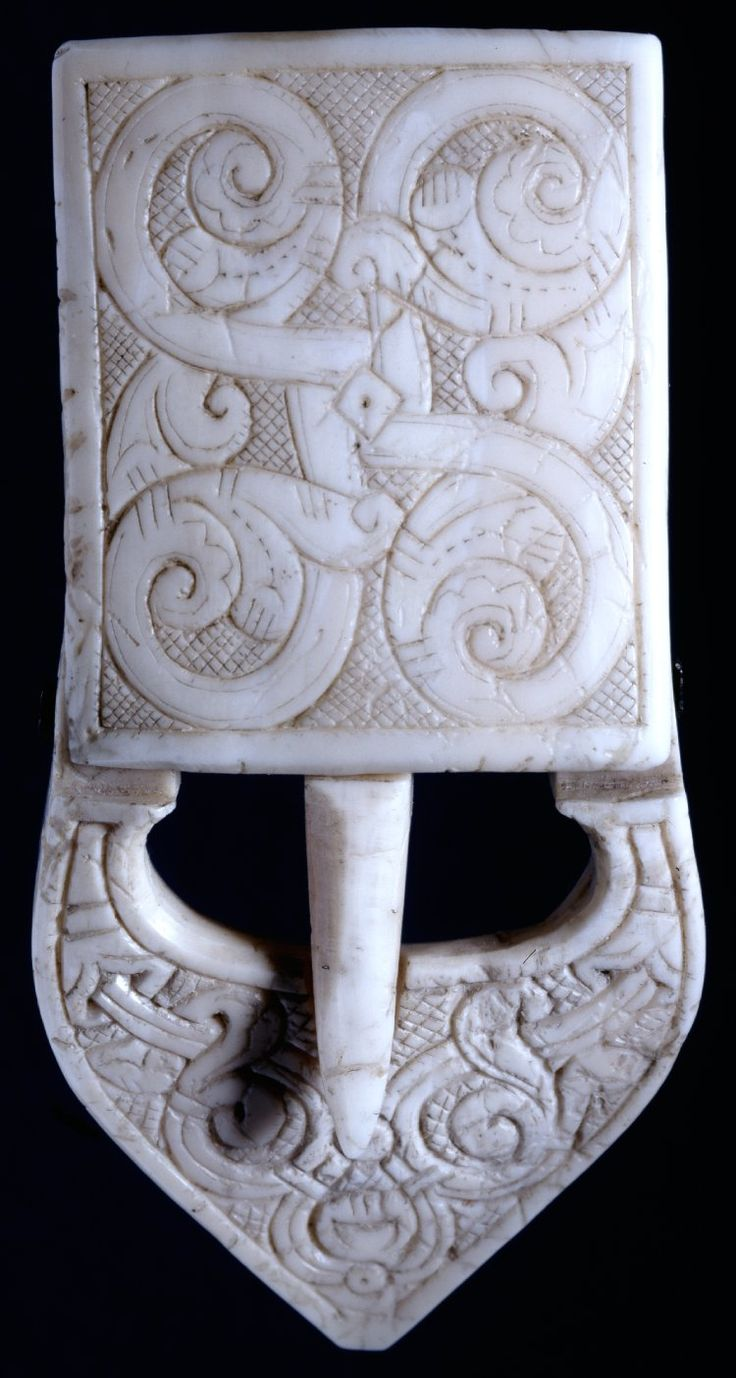 1150-1175 Scotland. Buckle; walrus ivory; upper part, with tongue, turning upon piece of copper wire; front surface: engraved with floral designs upon hatched background. -British Museum