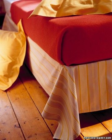 It's hard to decide which is the bigger eyesore: an exposed box spring or some of the froufrou dust ruffles currently on the market. One easy, low-cost solution is to cover the box spring with a drape of rectangular fabric.