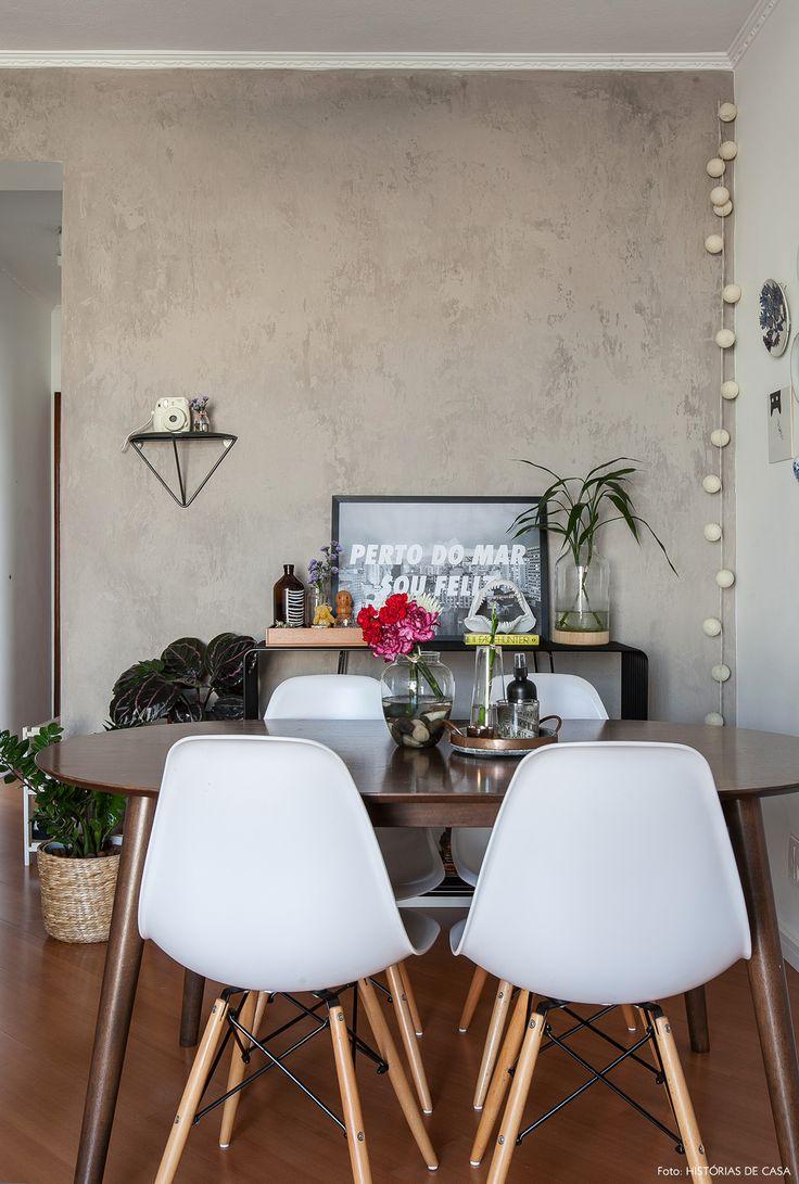 Parede de cimento queimado, mesa oval e cadeiras eames.