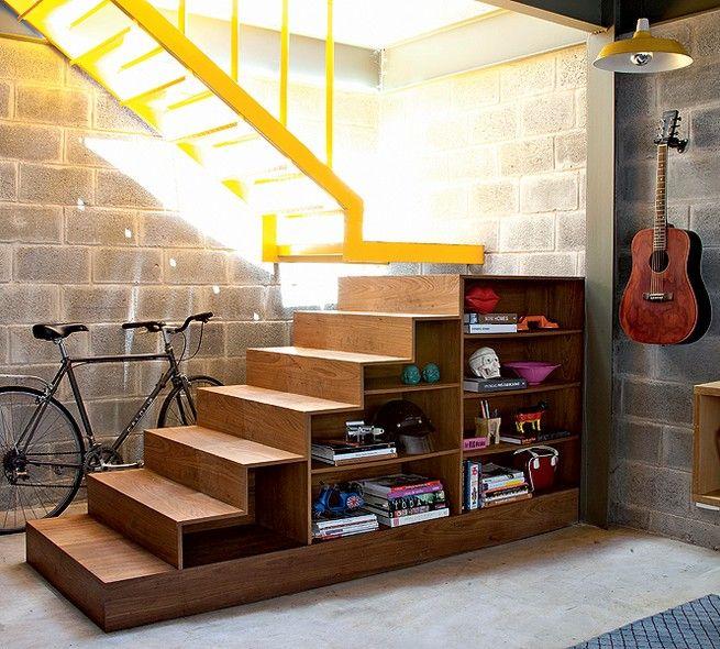 No projeto do escritório Arkitito, não só o espaço debaixo da escada é usado para guardar a bicicleta, como os degraus também são aproveitados. Na parte voltada para a parede, o morador guarda ferramentas e, na vista da sala, seus objetos de design