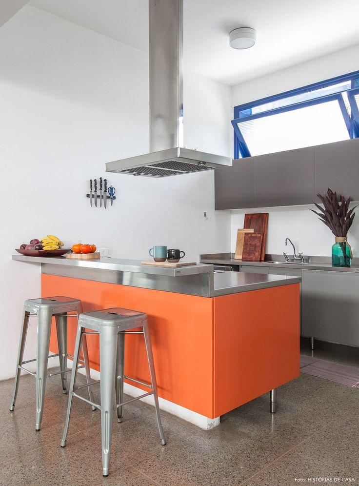 Cozinha decorada com cinza, laranja e matálicos.