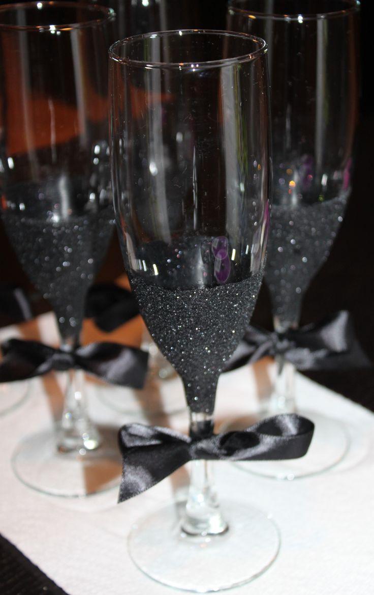 DIY Black Glitter Champagne Flutes. Use glue, paint brush, black glitter, and a…