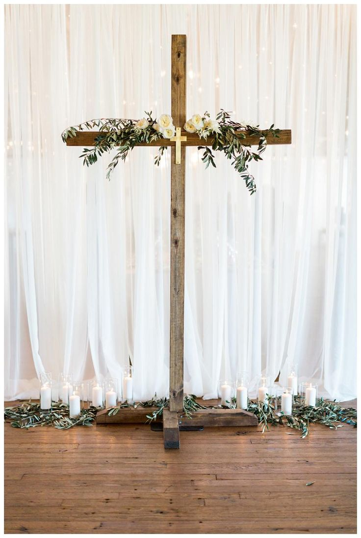 Wedding ceremony decor with a wooden cross, olive branches, drapery and candles at Summerour Studio in Atlanta. Event design by Molly McKinley Designs, florals by Victory Blooms. Image by Rustic White Photography.
