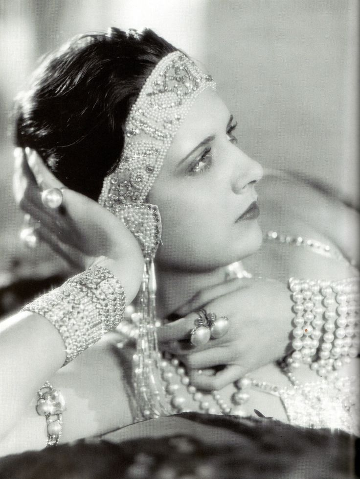 1930s actress Kay Francis wearing a bandeau (a tiara-inspired headpiece), bracelet, ring and necklaces of pearls. Attendance at movies was at record highs during the Depression as people sought to escape the dreariness of their lives by watching bejeweled, glamorous actresses on the big screen.  Photo of Francis and information about Mikimoto from Vintage Jewelry Design: Classics to Collect & Wear (Vintage Fashion Series) by Caroline Cox.