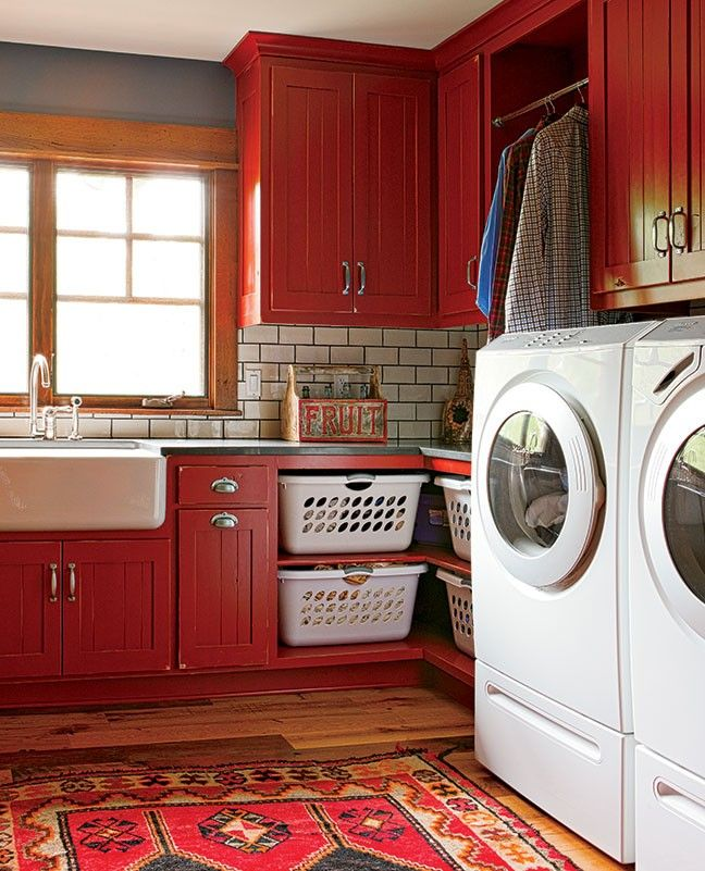 In Lynne and Jon Beaver's colorful laundry room cum office space cum butler's pantry, a barn provided the inspiration for the theme. The floors are reclaimed lumber from a tobacco barn in upstate New York. The cabinets, from Profile Cabinet and Design, are painted a classic barn red. Even the door leading to the kitchen was inspired by a vintage barn door. Loads of storage, convenient hanging space and lots of light almost make laundry fun.