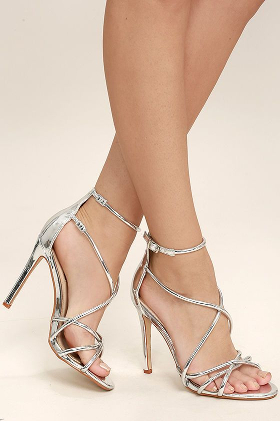 The Jeanne Silver Dress Sandals are a shining example of modern elegance! Metallic silver vegan leather straps cross over a peep-toe upper, and carry into an adjustable ankle strap (with silver buckle and elastic for fit).
