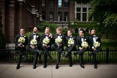 hombres vestidos de traje sentados en una cerca sosteniendo un ramo de flores
