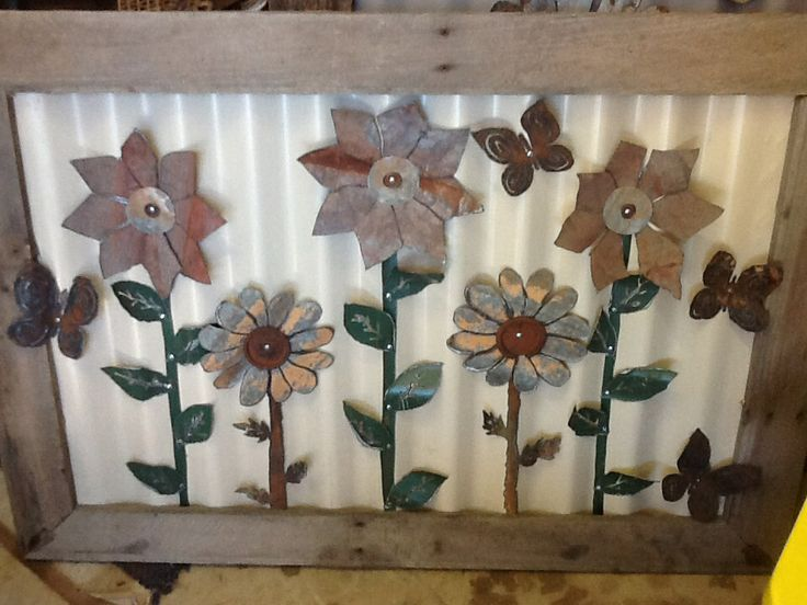 Metal flowers picture made fro old fencing materials and a packing sheet and pallets.