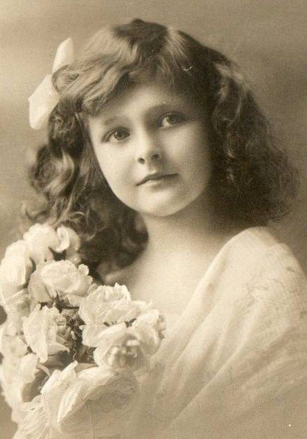 Beautiful little girl with white bow in her hair, holding white roses