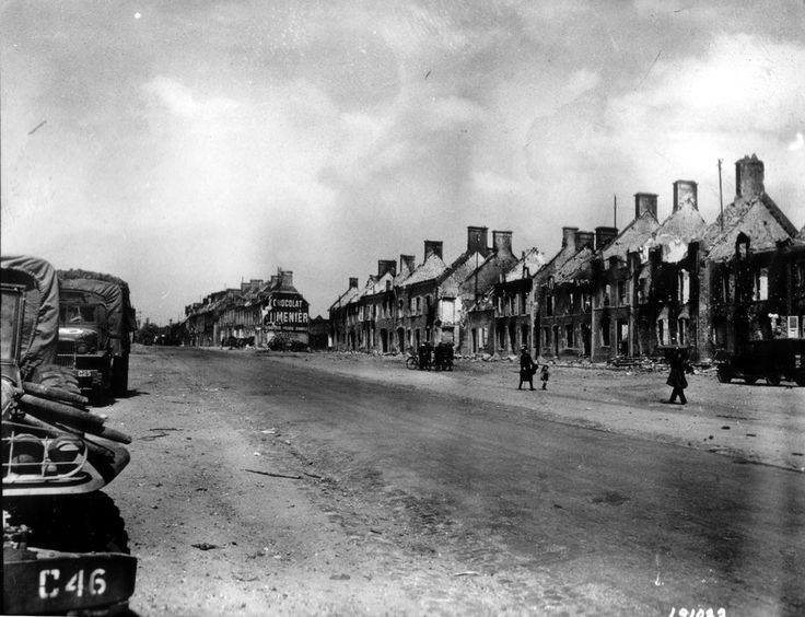 At left, a convoy led by a Dodge and GMC parked on the Place Nationale, with the main street in the middle, civilians find the damage: charred and ruined houses. The photo is taken at the beginning of the Place Nationale (now Pilgrim Albert Square named after the first mayor after the landing, Mayor introduced by the Americans) .. Top management Valognes. St. Paul is Lecacheux (senior executive) behind the photographer and the statue of Joan of Arc to the right behind the photographer.