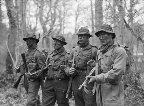 Trainees in a wooded area with their faces painted with camouflage paint, wearing American fatigue caps and gaiters and Carrying American 'Tommy' guns, during training at the Eastern Warfare School at Brockenhurst, Hampshire where they learn jungle tactics for the Pacific War, 2 February 1945. http://wrhstol.com/2rZhfJ7