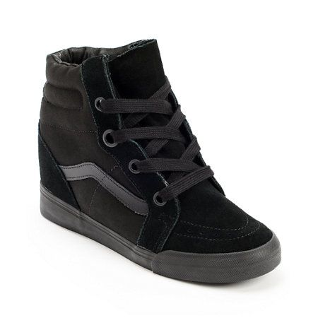 """Get a new take on street style with the Sk8-Hi Black wedge sneakers for girls from Vans. These all Black wedge shoes from Vans have a 3"""" heel with a micro-waffle tread for while the upper is made of a textile and suede material so you can rock some classi"""