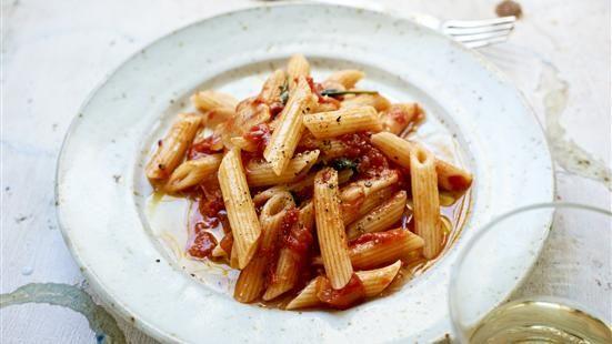 Fräs vitlök i olivolja några minuter utan att den får färg. Häll på tomater, vin, vatten. Krydda med lite strösocker, salt och peppar. Lägg i basilika och låt puttra ca 25 minuter. Smaka av igen. Blanda med nykokt pasta. Servera med nyriven parmesan och lite god olivolja att ringla över.