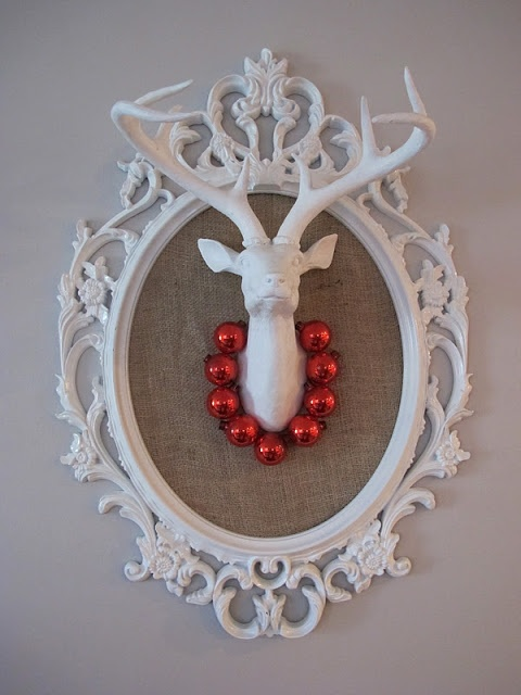 What a nice take on the stark white deer head... framed in a lovely picture frame and dressed for the season with a necklace of ornaments