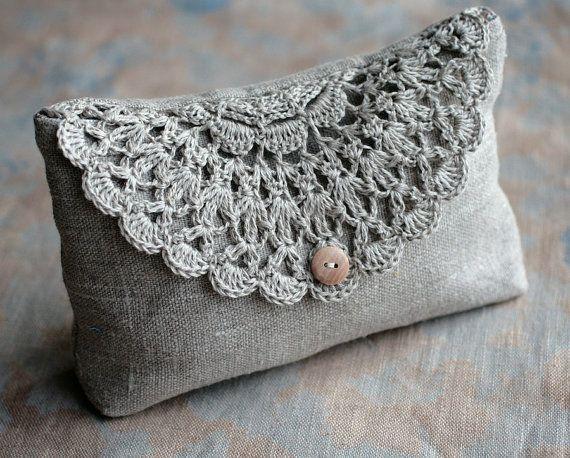Esta elegante bolsa/embrague es de lino puro y se cierra con botón cubierto lino y detalle de tapete de ganchillo de la mano. Forrado con tela de